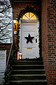 Brick house with festively decorated front steps and door