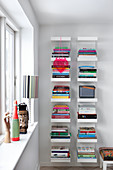 Books stacked on vertical bookshelves next to window
