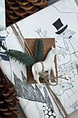 Weißes Pferd und Tannenzweige auf einem verpackten Geschenk