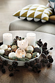 White candles and Christmas baubles on plate in wreath of pine cones