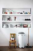 Crockery and kitchen utensils on fitted shelves in niche in white wall