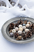 Festive arrangement of embroidered felt balls and pine cones