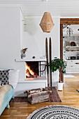 Fire in open corner fireplace in Scandinavian-style living room