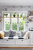 Sitzbank mit Kissen am Fenster in der Küche mit Bohoflair