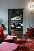 Glamorous living room in shades of red with view through open double doors
