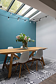 Shell chairs at wooden table next to blue wall and on patterned floor tiles