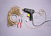 Craft utensils for making bunny decorations: cord, wire, hot glue gun and pompom
