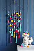 Handmade wall-hanging of pompoms and tassels
