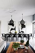 Tisch und Stühle in Schwarz im offenen Wohnraum mit hoher Decke