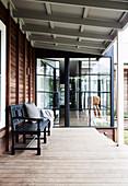 Schwarze Bank auf der Veranda mit Dielenboden am Holzhaus