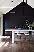 Barhocker am Marmortisch in moderner Küche mit offener Decke