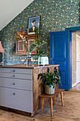 Bänkchen mit Zimmerpflanze an der Kücheninsel vor Blümchentapete