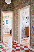 Chequered pattern on wooden floor in hallway with floral wallpaper