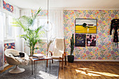Retro armchairs and floral wallpaper in light-flooded seating area