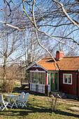 Rotes Schwedenhaus mit Wintergarten und Garten im Frühling