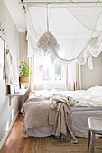 Small, white and grey bedroom with canopy over bed