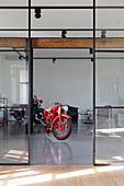 Motorbikes in living room with glass and steel wall