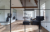 View through glass and steel wall into minimalist living room