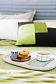 Biscuits and cup of espresso on tray on bed with green bed linen