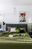 Graphic patterns in bedroom with green bedspread on bed with upholstered headboard