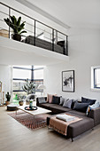 Grey corner sofa in modern, open-plan interior with gallery