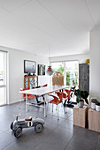 Vilac ride-on car in open-plan dining area with orange designer chairs