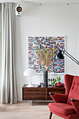 Designer lamp on low sideboard below artwork with rectangles of colour