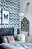Wallpaper with graphic pattern in child's bedroom decorated in blue and grey