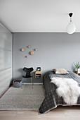 Sheepskin rug on bed in simple bedroom in shades of grey