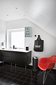 Red designer chair in black-and-white bathroom with sloping ceiling