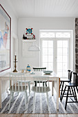 Various spoke-back chairs around table in white dining room