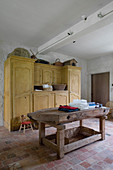 Old workbench and yellow cupboard in rustic laundry room