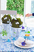 Handmade moss balls with feathers decorating Easter table