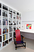 Colourful designer chair and white shelves in study