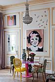 Verschiedene Stühle am pinken Tisch vor Kassettenwand mit Gemälden