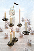 Christmas arrangement of miniature candlesticks and white origami stars
