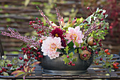 Autumn arrangement with dahlias, hawthorn berries, ling and medlar fruits