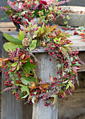 Wreath of hawthorn berries, ling, medlar fruits and leafy branches