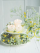 Bouquets and wreath of cow parsley and buttercups on plate around candles on cake stand for 60th birthday