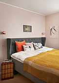 Spice shades in classic bedroom with pale pink walls