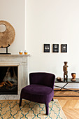 Purple easy chair next to sculpture on mantelpiece in living room