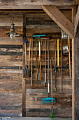 Gardening tools hung on board wall made from reclaimed wood