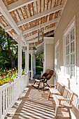 Rocking chair and old bench on veranda of white wooden house