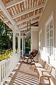 Schaukelstuhl und alte Bank auf der Veranda am weißen Holzhaus