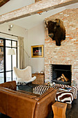 Buffalo head above open fireplace in rustic living room