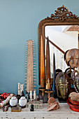 Collection of curiosities and old gilt-framed mirror against blue wall