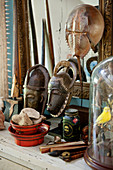 Collection of curiosities including masks, flea-market finds and horseshoe crab