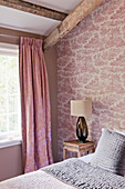 Patterned curtains in bedroom with toile de jouy wallpaper