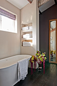 Free-standing bathtub in bathroom with shelves in niches and flower arrangement with amaranth
