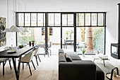 Dining table and sofa in front of glass wall overlooking terrace